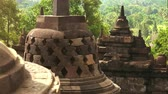 kamie�� : Perforated stupas illuminated by bright sunlight against tropical forest on background. Architectural elements of Borobudur Buddhist temple in Magelang, Central Java, Indonesia. Camera zooms out.