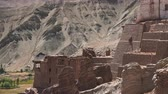 оставаться : Ruins of Basgo Palace beside Bazgo Gompa monastery against gorgeous mountainous terrain illuminated by sunlight and clear blue sky. Remains of ancient building. Ladakh, India. Camera zooms out.