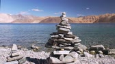 tibetano : Traditional Buddhist stone pyramid or rock tower against clear water of Pangong Tso lake, Himalaya mountains and blue sky. Concept of serenity, meditation and zen. Ladakh, India. Panoramic view. Stock Footage