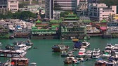aberdeen : HONG KONG - OCT 27, 2017: Boats and yachts swaying on waves against cityscape on background. Floating village. Historical place and popular touristic landmark. Aberdeen harbor, Hong Kong. Zooming out Stock Footage