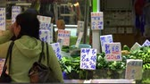 hieroglyf : HONG KONG - NOV 4, 2017: Female buyer standing beside counter with green vegetables and looking at price tags. Greengrocers shop selling food at traditional Asian open market. Local retail trade. Dostupné videozáznamy