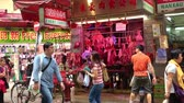вывеска : HONG KONG - NOV 4, 2017: butcher shop or store with hanging cuts of meat on sale at traditional Asian street market, man washing asphalt with hosepipe in front of it and people passing by camera. Стоковые видеозаписи