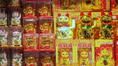 vzpřímený : HONG KONG - NOV 2, 2017: Small figures or statues of beckoning or lucky cat with moving upright paws in plastic packaging displayed in shop or store window. Traditional Chinese symbol of good luck.
