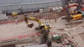 housenka : SINGAPORE - OCT 18, 2017: Excavators, cranes and hard hat workers working at urban construction site. Heavy equipment vehicles or machines moving and digging ground. Top view. Fast motion video. Dostupné videozáznamy