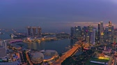 SINGAPORE - OCT 19, 2017:  Speed motion video with shift from evening to night, sunset at Singapore. Aerial view of light show at Marina Bay Sands hotel. City with skyscrapers and futuristic buildings