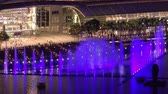 SINGAPORE - OCT 19, 2017: Fantastic daily light show in front of Marina Bay Sands Hotel and Shopping Mall. Beautiful view of tall fountain water changing colors. People enjoying amazing performance Стоковые видеозаписи