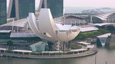 SINGAPORE - OCT 20, 2017: Futuristic building of ArtScience or Lotus Flower Museum against Marina Bay Sands hotel and sea port with cargo ships on background. Amazing urban landscape.