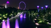 SINGAPORE - OCT 21, 2017: Magnificent fountains at Dragonfly Lake in front of Gardens by the Bay and Singapore Flyer wheel on background. Tranquil water pond illuminated at night