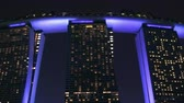 SINGAPORE - OCT 21, 2017: Fantastic night view of Marina Bay Sands hotel and shopping mall illuminated in dark sky by blue light. Popular touristic landmark zooming out video