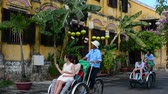 Pedicabs and tourists on the street of Hoi An