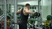 suor : Athletic Young Male Does Dumbbell Exercises at Gym