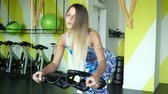 bacaklar : Attractive girl on an exercise bike Stok Video