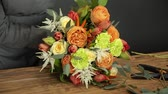 kwiaciarnia : Florist prepares a bouquet of flowers for sale Wideo