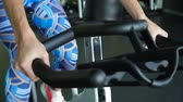 tenký : Exercise bike - A woman exercising on a stationary bike in a gym