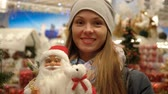 escolher : Portrait of a girl in a supermarket on the background of Christmas decorations