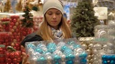 seçen : A young beautiful girl walks by the supermarket and chooses. Slow motion. Stok Video