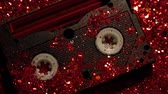 plástico : Black video cassette on the background of red glitter Stock Footage