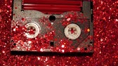 parçacık : Black video cassette on the background of red glitter Stok Video