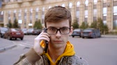 Concentrated young man with glasses holding a phone near his ear Stock Footage
