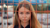 конфликт : Frustrated girl put her hands on the grid, fencing