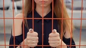 moda : Frustrated girl put her hands on the grid, fencing
