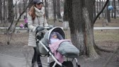 pram : Mother walking with a pram in the park. Stock Footage