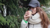 coat : Beautiful young girl wearing in a grey cap and white coat drinking coffee from a disposable Cup. Spruce on background