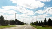 путешествие : A car ride down road  in residential suburban neighborhood looking at trees, clouds, houses and landscape - Travel and leisure concept