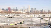 yat : Boat harbor on Lake Michigan with snow and ice - Chicago skyline in background Stok Video