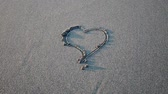 desenhado : Heart drawn on the sand erasing wave
