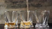 três : Pouring whiskey in three glasses
