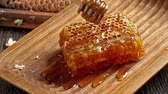 cera de abelha : Honeycombs with pouring honey from wooden honey dipper Vídeos