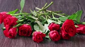 prezent : Valentines days arrangements with red roses and red gift box over gray background Wideo