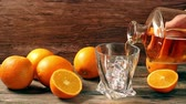 hard : Pouring whiskey from bottle to glass over gray background with orange Stock Footage