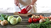 Woman slice vegetables. Woman slice paprika on wooden table. Rustic style. Stock Footage