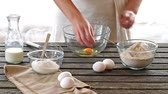 dough : Woman breaking eggs into a bowl. Rustic style.