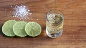 Pouring tequila in glass with lime slices and salt