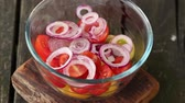 Mixing salad of tomatoes and onions by wooden spoon