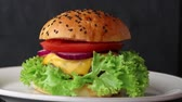 lanches : Rotating ceramic plate with fresh homemade burger over dark black  background