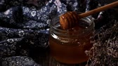 Open glass jar of liquid honey with honeycomb and honey dipper inside, bunch of dry lavender. Dark rustic style.