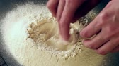 черный : Female hands break the egg into flour for making dough over black table