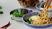 noodle dish : Taking by bamboo chopsticks noodles from asian ramen soup with feta cheese, noodles, spring onion and mushrooms, served sliced boiled egg over white kitchen table Stock Footage