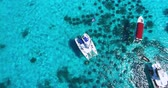 Racha Island Beach. Thailand, Phuket. Yachts , Catamarans and Boats sailing in crrystal clear blue water of ocean. Take off from ocean to sky. Catamaran in center of view. Aerial view. 4K.