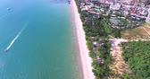 Aerial view flying over Thai island towards beautiful green mountains and white sandy beach. Krabi island, Thailand