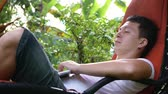 money thai : Dream work. Serious man works in the tropical place, lay on hammock. The happiest work. Close plan. Freelance. Slow motion