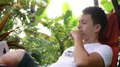 money thai : Dream work. Serious man hard works in the tropical place, lay on hammock and use notebook. Close plan. Freelance. Slow motion