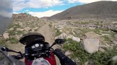 mongolia : motorcyclist driving in mountains with rocks and river