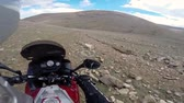 mongolia : motorcyclist driving on road in mountains with rocks