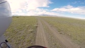 estepe : motorcyclist driving on road in steppe with mountains