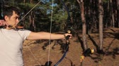 bowman : The young man is shooting from the sports bow in a sunny forest. Stock Footage